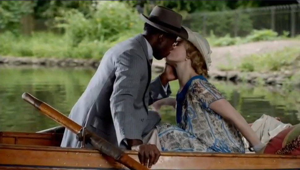 black man and white woman in dark green rowboat
